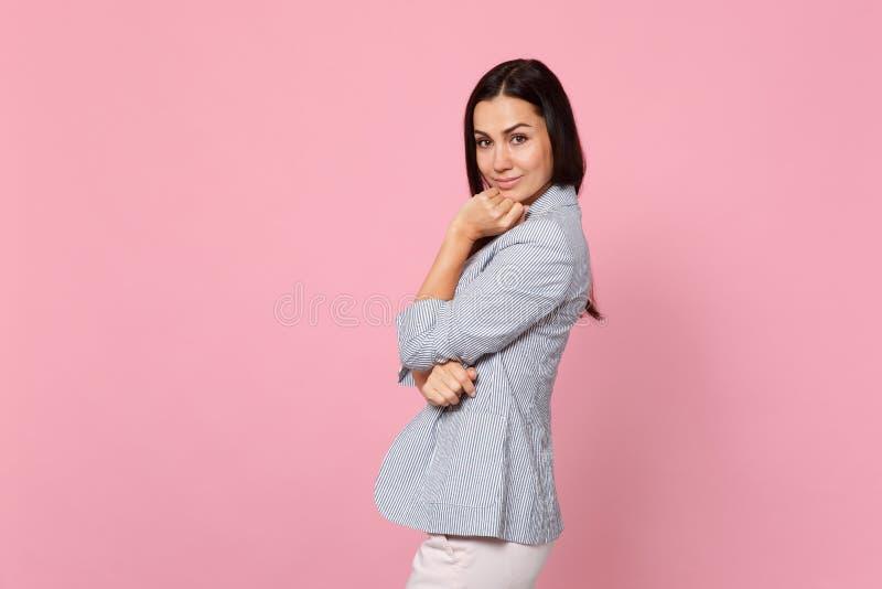 La vue de côté de la jeune femme attirante dans la veste rayée regardant la caméra, a mis l'appui vertical de main sur le menton  image libre de droits