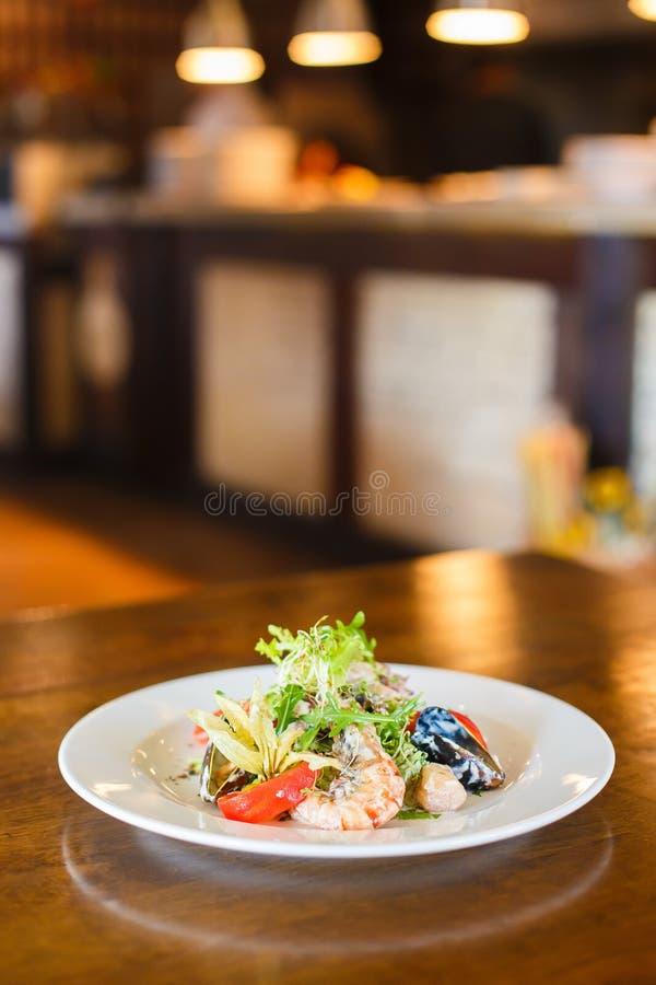 La vue de côté verticale de la salade de fruits de mer a compris la laitue, les moules, la crevette et les tomates décorées de photos stock