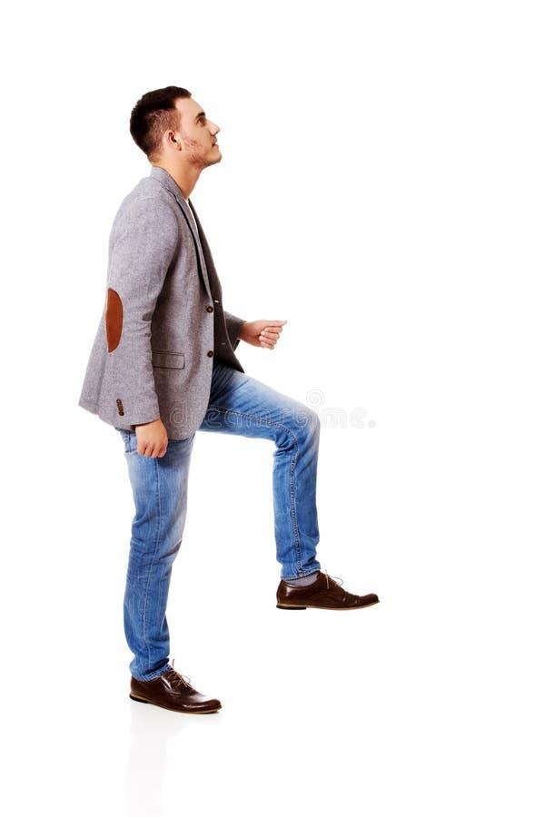 La vue de côté d'un homme d'affaires monte les escaliers photo libre de droits