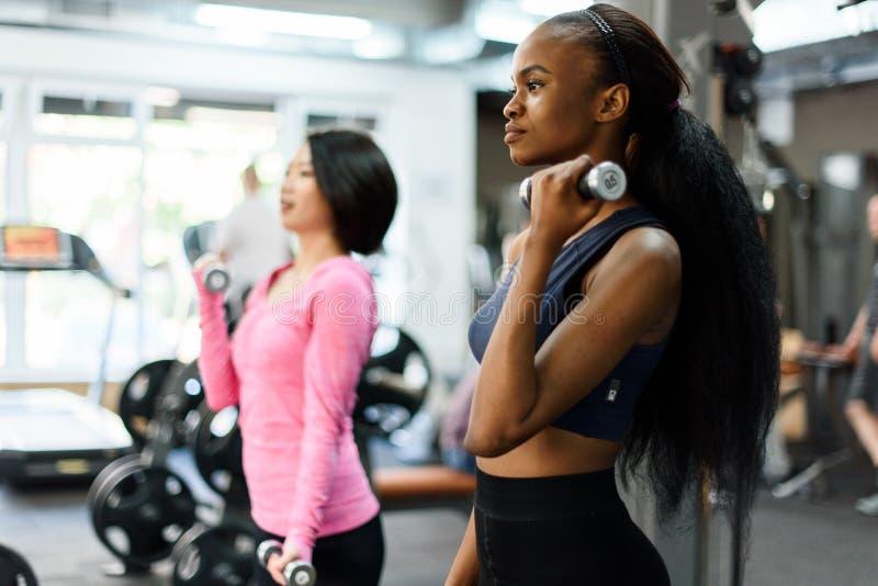La vue de côté de l'instructeur noir mince de forme physique d'afro-américain et la belle femme asiatique faisant l'exercice de f image stock