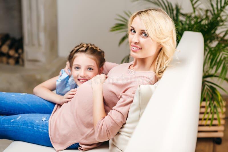 La vue de côté de la fille de sourire touchant les mères enceintes se gonflent tout en se reposant sur le sofa photo libre de droits