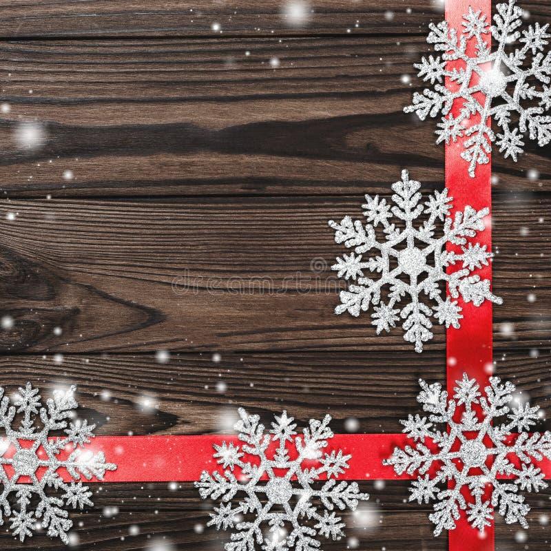 La vue de ci-dessus d'une inscription de Joyeux Noël sur le fond en bois de brun foncé avec le ruban rouge et les jouets faits ma image stock