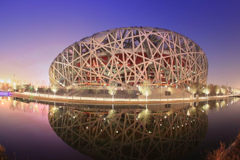 La vue de coucher du soleil du stade de Pékin s'est reflétée dans le lac photos libres de droits