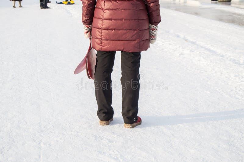 La vue de derrière d'une femme dans des vêtements d'hiver se tenant dans la neige en parc et tenant un traîneau, glace, attente l photos libres de droits