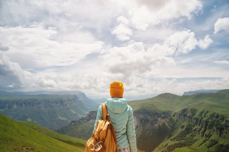 La vue de derrière d'une fille de touristes avec un sac à dos est s'élevante et regardante les vallées vertes de montagne et image stock