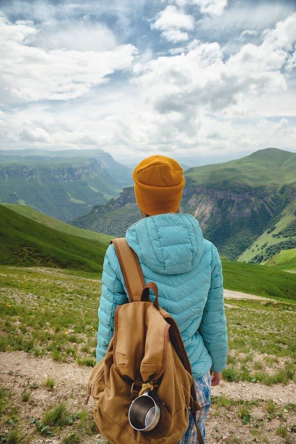 La vue de derrière d'une fille de touristes avec un sac à dos est s'élevante et regardante les vallées vertes de montagne et photographie stock libre de droits