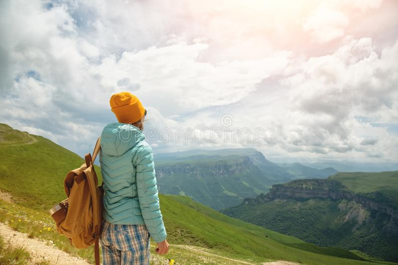 La vue de derrière d'une fille de touristes avec un sac à dos est s'élevante et regardante les vallées vertes de montagne et photos stock