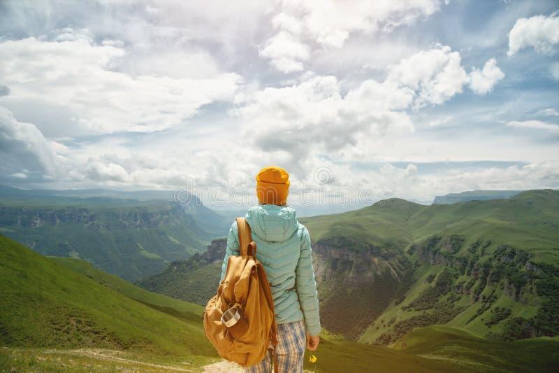 La vue de derrière d'une fille de touristes avec un sac à dos est s'élevante et regardante les vallées vertes de montagne et image libre de droits