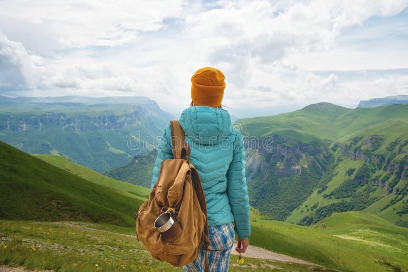La vue de derrière d'une fille de touristes avec un sac à dos est s'élevante et regardante les vallées vertes de montagne et photographie stock