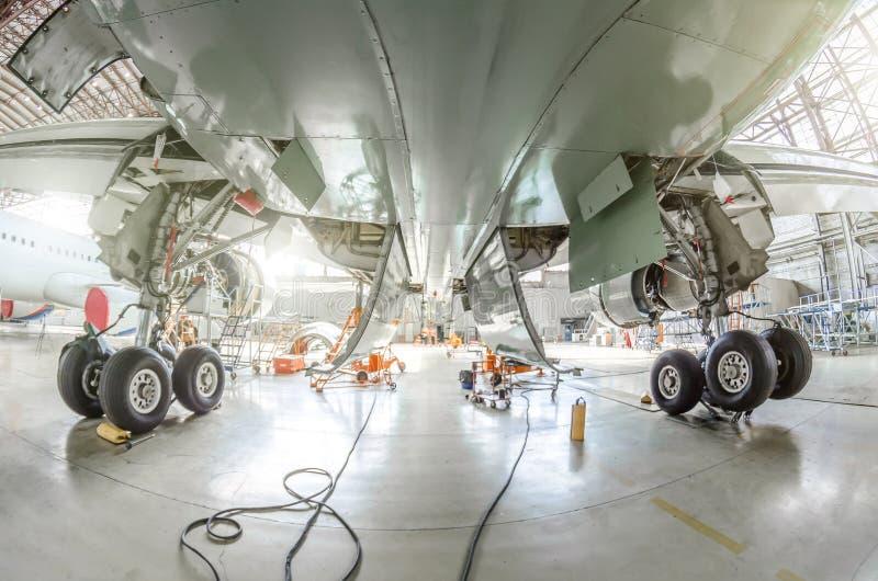 La vue de dessous les avions entre les supports de châssis de roule dedans le hangar image libre de droits