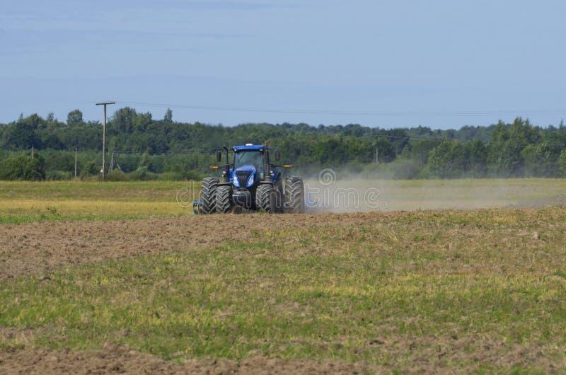 La vue de face du tracteur laboure le champ avec la poussière de tourbillonnement photos libres de droits