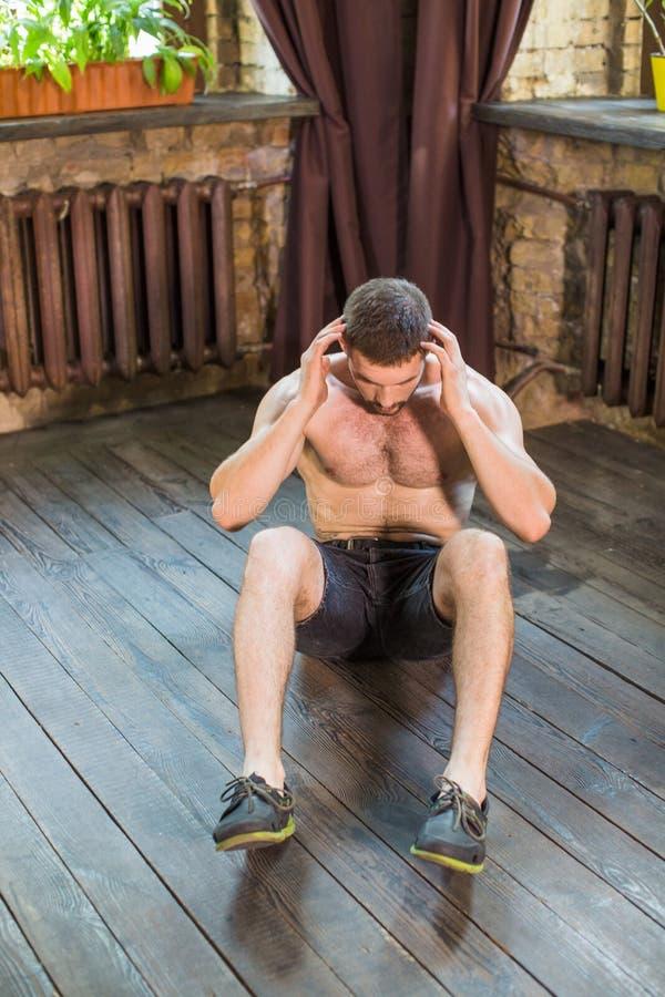 La vue de face de l'homme que faire se reposent se lève et craque sur le plancher à la maison photo libre de droits