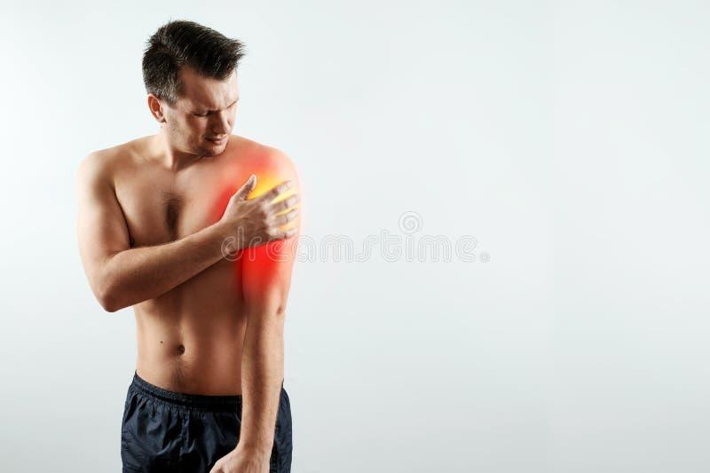 La vue de face, l'homme tient ses mains sur l'avant-bras, la douleur dans sa main, douleur dans l'épaule a accentué en rouge photo stock