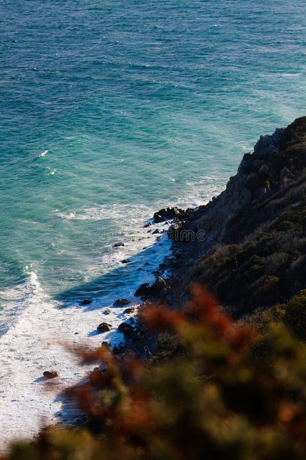 La vue de la falaise au rivage rocheux du cap lavé par la mer photos stock