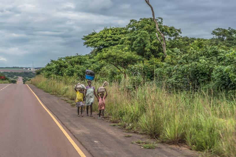 La vue de la femme avec des enfants marche avec la charge principale, le long du bord de la route, paysage tropical comme fond photos libres de droits