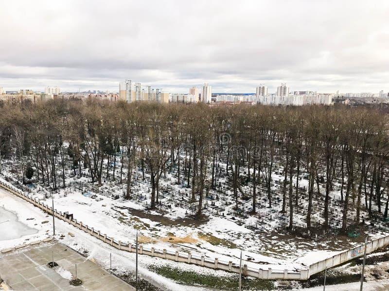 La vue de la fenêtre du vieux cimetière de ville en parc d'une taille avec des arbres et des maisons pendant l'hiver images stock