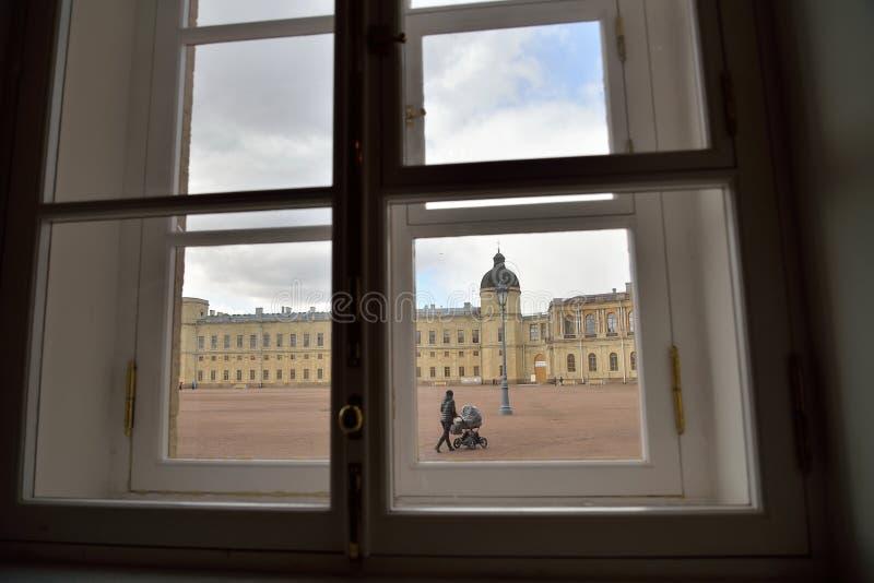 La vue de la fenêtre : une femme avec une poussette intervenant photo libre de droits
