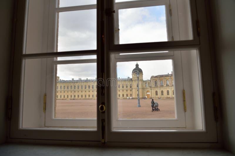 La vue de la fenêtre : une femme avec une poussette vient sur le b photo libre de droits