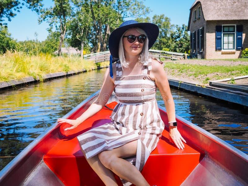 La vue de la fille avec les cheveux blonds et le chapeau bleu se reposent sur un tour de bateau à la rivière dans le village néer photos stock