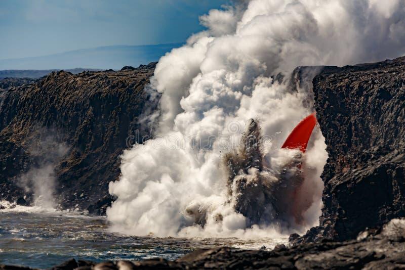 La vue de jour aérienne du dessus de la cascade a formé l'écoulement de la lave rouge du volcan en Hawaï éclatant dans la mer photos stock