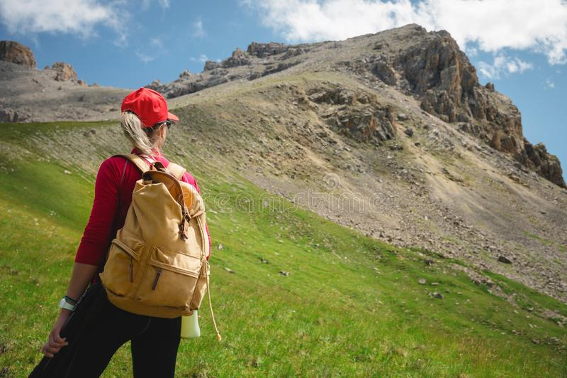 La vue de l'athlète arrière de fille dans des lunettes de soleil rouges d'un chapeau et un sac à dos jaune se tient sur une pente photographie stock