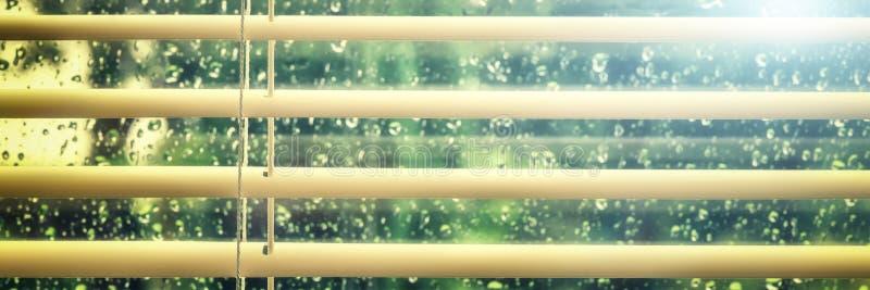 La vue de la fenêtre humide avec la pluie chute par des aveugles photo stock