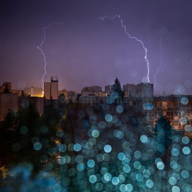 La vue de la tempête de ville par la fenêtre humide avec la pluie brouillée chute photographie stock