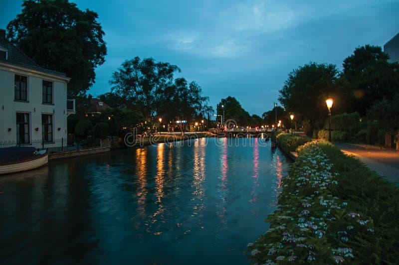 La vue de nuit du canal bordé d'arbres large, le pont et la lampe signalent l'éclairage à l'aube dans Weesp photographie stock