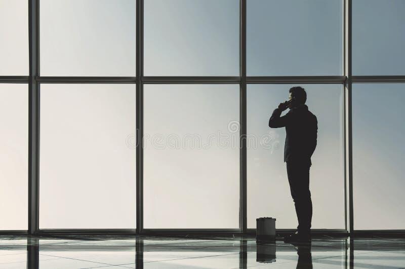 La vue de silhouette du jeune homme d'affaires se tient dans le bureau moderne avec les fenêtres panoramiques photos libres de droits
