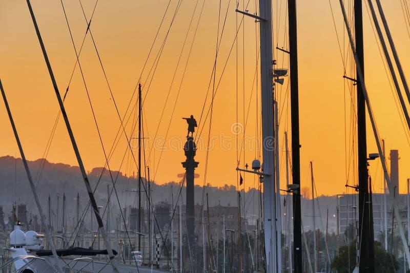 La vue de silhouette de statue de Columbus par des arbres et des linceuls des bateaux a amarré dans le port au coucher du soleil  photo stock