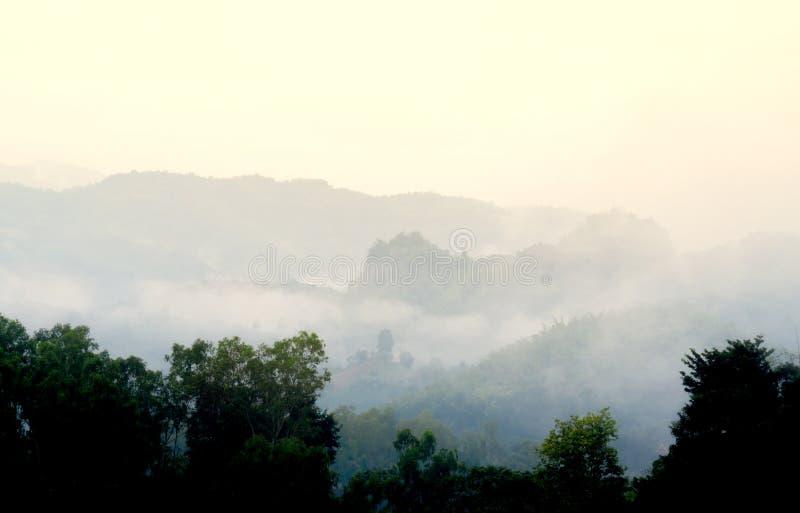 La vue des couches de la montagne dans le matin brumeux le brouillard forme dans la vallée comme soleil s'allumant vers le haut d photo libre de droits