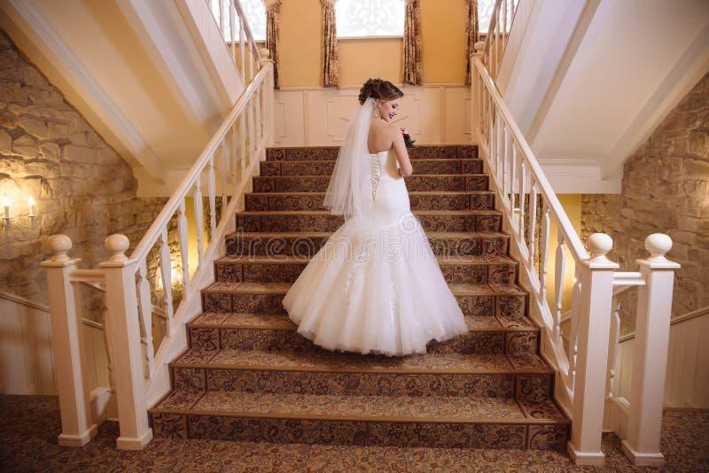 La vue du dos, la jeune mariée monte les escaliers dans une belle robe serrée, tourne autour et rit photographie stock libre de droits