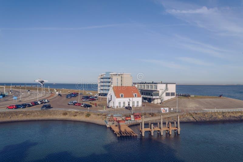 La vue du ferry sur l'hôtel débarque la maison d'extrémité et de poivre avec les voitures garées image stock
