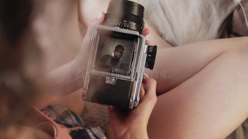 La vue en gros plan de la jeune femme dans des pyjamas tient le vieux photocamera Couples multiraciaux prenant des photos, poses  images libres de droits