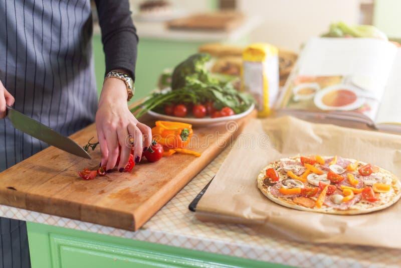La vue en gros plan de la jeune femme s remet des légumes de coupe à bord pour la pizza selon le livre de recette photo stock