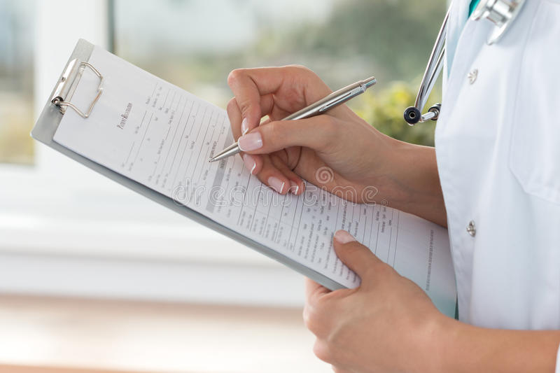 La vue en gros plan du docteur féminin remet le registratio patient remplissant photos stock