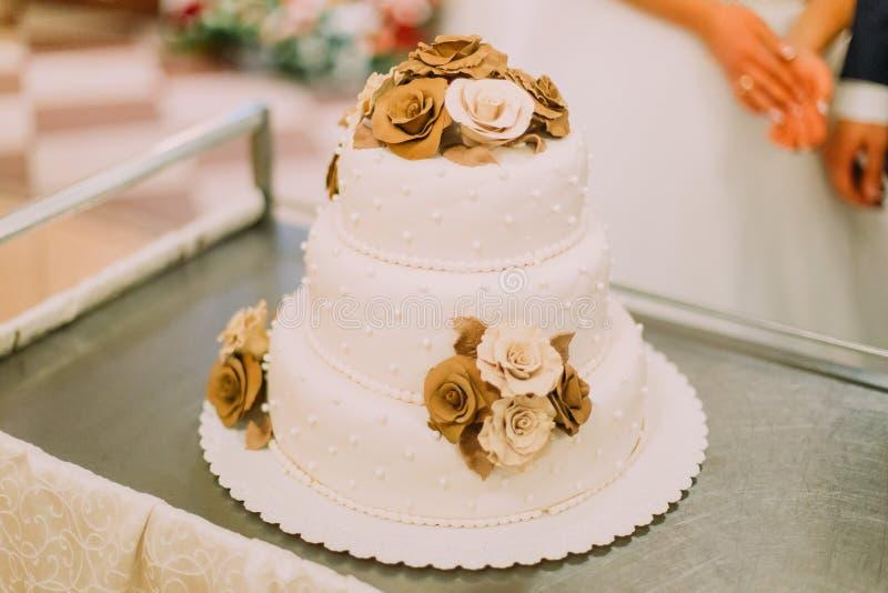 La vue en gros plan du gâteau de mariage blanc de trois-plancher décoré du chocolade fleurit image stock