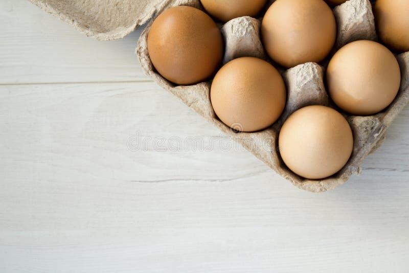 La vue en gros plan du poulet cru eggs dans la boîte à oeufs sur le fond en bois blanc photo stock