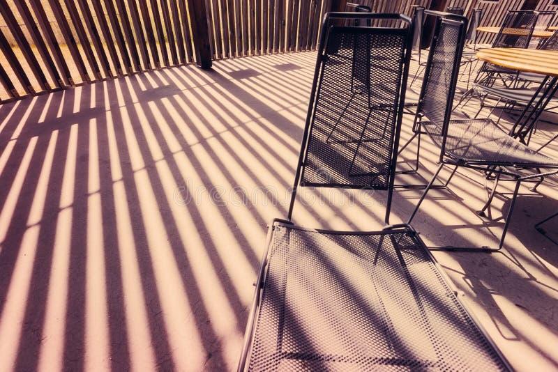 Chaises de maille en métal et rayures de lumière du soleil photographie stock libre de droits