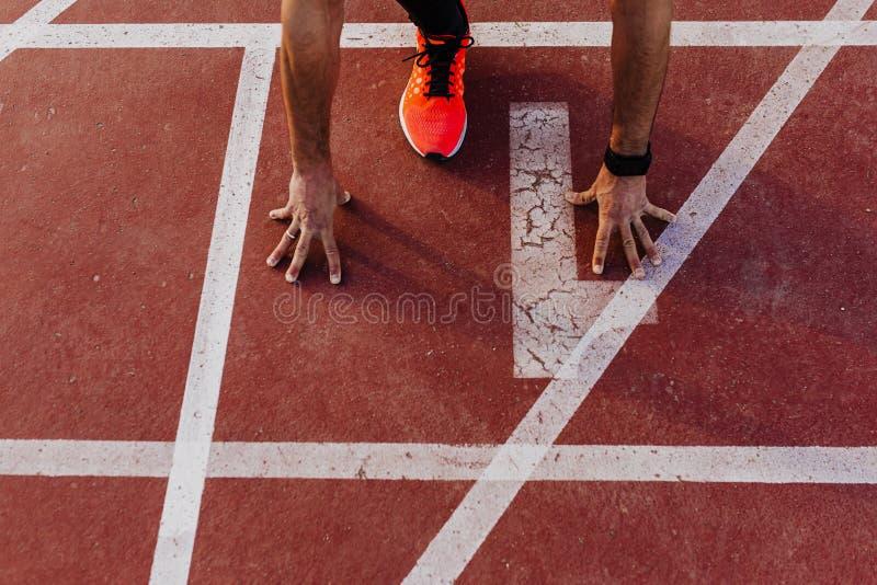 La vue haute étroite du jeune athlète musculaire est au début des voies de course rayent au stade Concept de sports photos stock