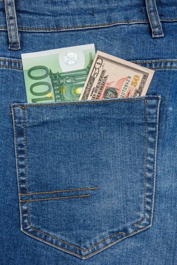 La vue haute ?troite aux billets de banque de 100 euros et des 50 dollars collant de l'des blues-jean empochent photos stock