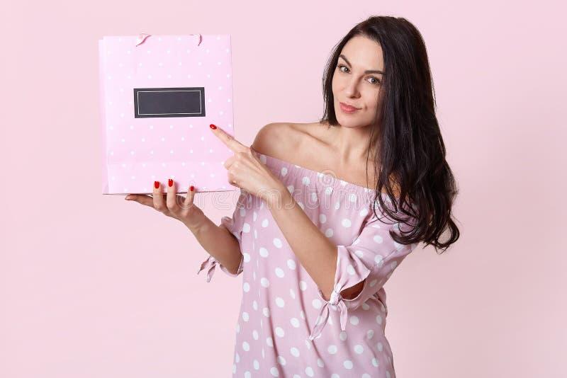 La vue horizontale des points européens agréables à regarder de femme au sac de cadeau, montre l'espace libre pour votre contenu  image stock