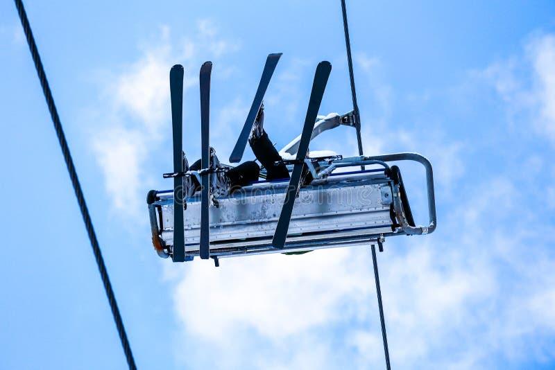 La vue inférieure des skieurs ont un amusement sur l'ascenseur de chaise photographie stock libre de droits