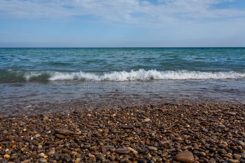 La vue inférieure sur la vague de mer roule sur le rivage du bardeau image libre de droits