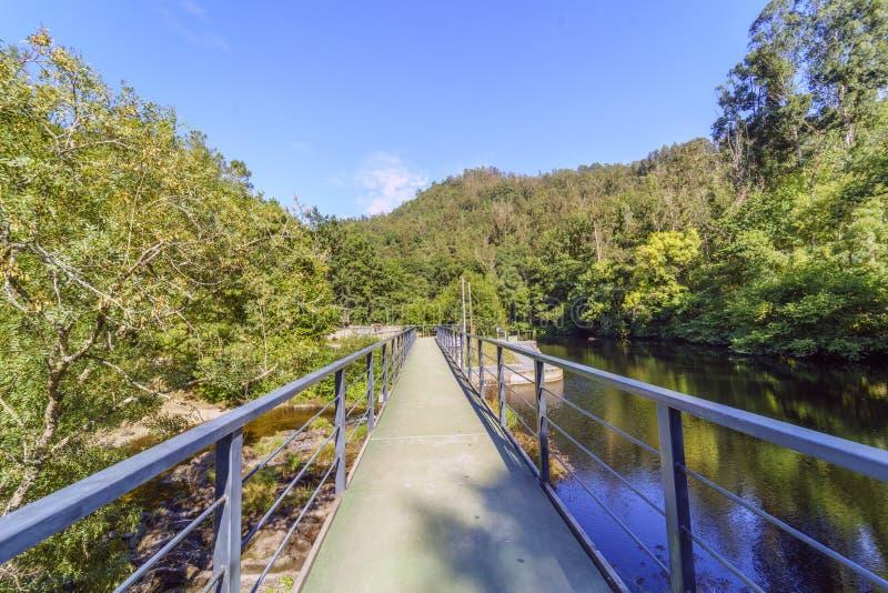La vue longitudinale d'un pont au-dessus d'une partie large du courant de montagne a appelé le ` Chelo photographie stock libre de droits