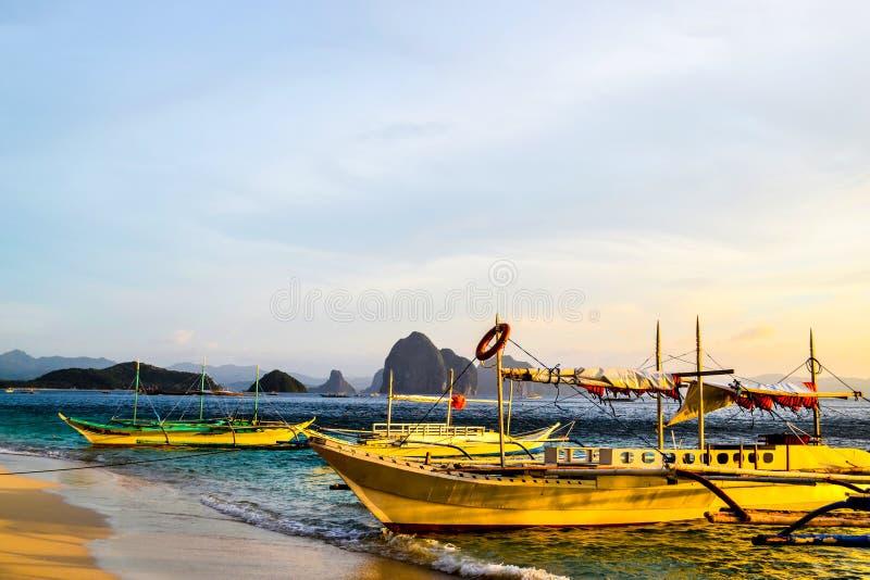 La vue merveilleuse du ciel de coucher du soleil miroitant des falaises de mer sur l'horizon et les bateaux a amarré à côté d'une photo libre de droits