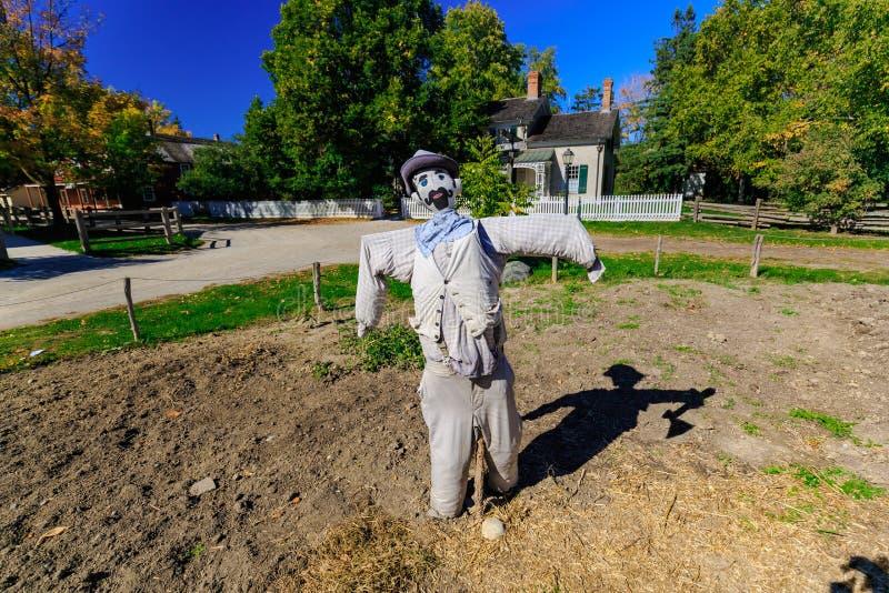 La vue mystique de l'épouvantail et son ami d'ombre se tenant dans la ferme font du jardinage et sont prêts pour la partie de Hal photo libre de droits