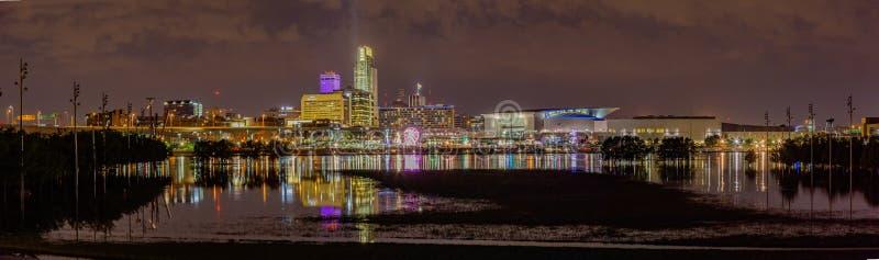 La vue panoramique de scène de nuit de la façade d'une rivière d'Omaha avec le Conseil en crue de parc du bord de la rivière de T photos libres de droits