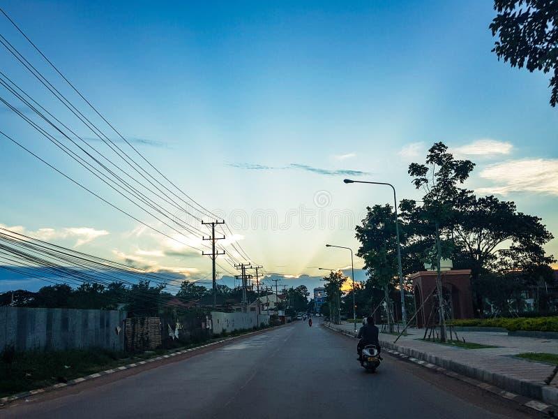 La vue parfaite la route avec le hangar de l'éclairage de coucher du soleil au Laos image stock