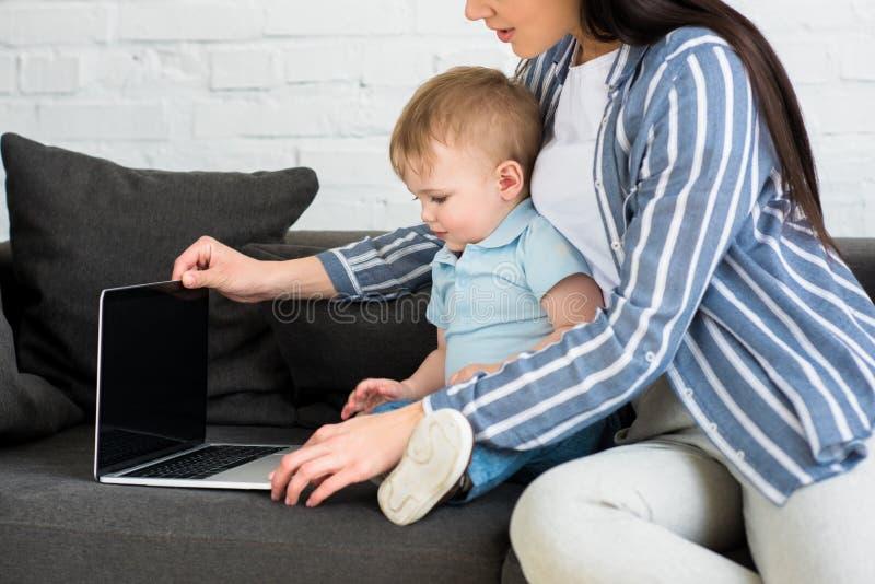 la vue partielle de la mère avec l'ordinateur portable et le bébé mignon sur le sofa fonctionnent à la maison et la vie photo stock
